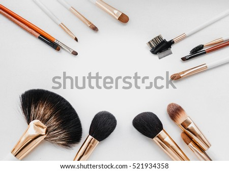Flat top view set of essential professional make-up brushes on white background. Copy space for your text.