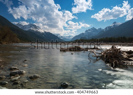 flat water of rural river with stones at blue sky in spring