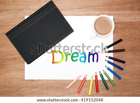 flatlaly of stationery. a black hard cover book, white drawing paper, a cup of coffee and colouring pencils. dream text - stock photo