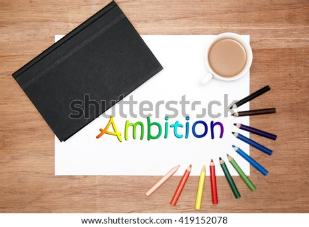 flatlaly of stationery. a black hard cover book, white drawing paper, a cup of coffee and colouring pencils. ambition text - stock photo