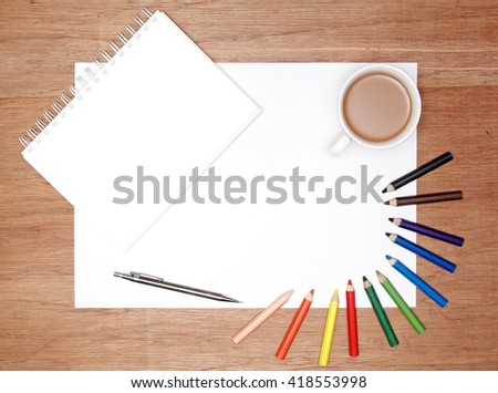 flatlay of stationeries. color pencil. white spiral bound book. a cup of coffee and a blank white paper.  - stock photo