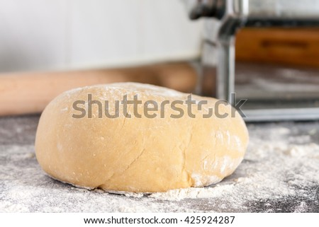 Flattened ball of fresh pasta dough on a floured surface