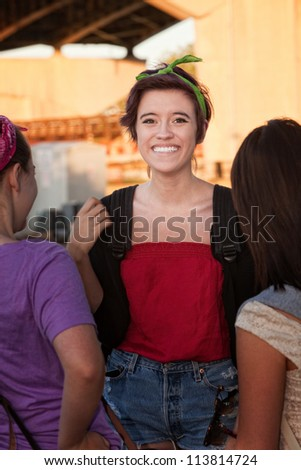 Flattered teenage girl talking with friends outdoors - stock photo