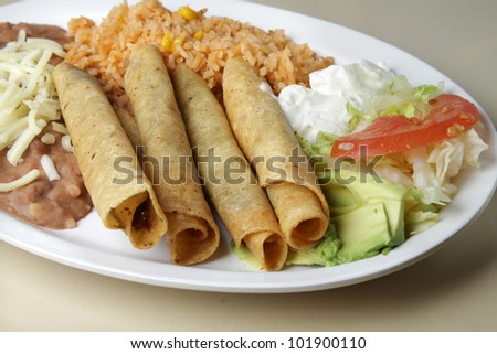 Flautas / Typical Mexican plate. Rolled tacos served as a meal with a side of beans and rice. - stock photo