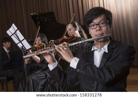 Flautist holding and playing the flute during a performance - stock photo
