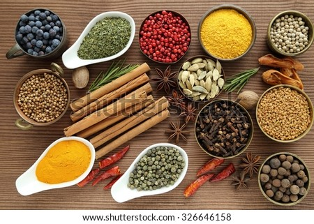 Flavorful, colorful spices in ceramic and metal bowls on wooden background. - stock photo