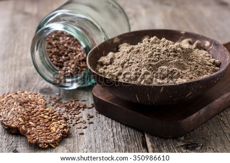 flax flour in a bowl, flax seed crackers,  flax seeds in a glass jar on a wooden background ( gluten-free diet ) - stock photo
