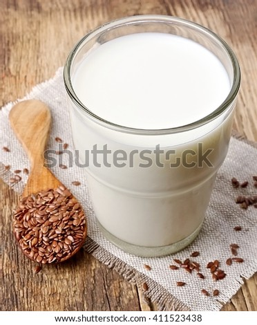 Flax milk and flax seed on a wooden background - stock photo
