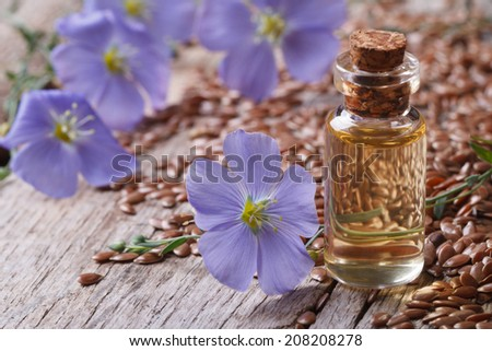 flax oil in a glass bottle closeup on a background of flowers and seeds horizontal  - stock photo