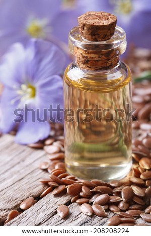 flax oil in a glass bottle macro on a background of flowers and seeds vertical  - stock photo