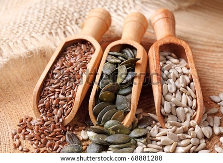 Flax, pumpkin and sunflower seeds in wooden spoons - stock photo