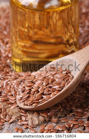 Flax seed in a wooden spoon and a bottle with oil. vertical macro  - stock photo