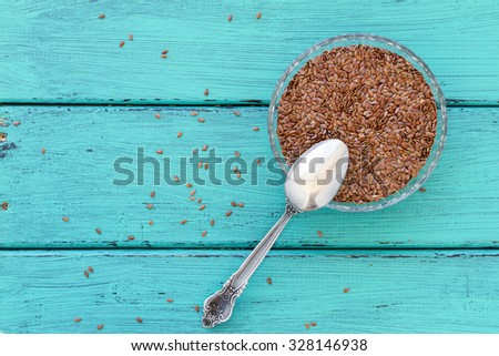 Flax seeds in a bowl with a spoon on a wood vintage background. Flax seeds are rich with fatty acid, omega 3 and fiber