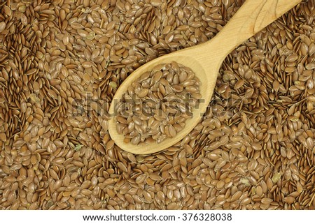 flax seeds in a wooden spoon abstract background