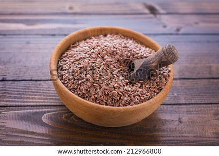 Flax seeds in bowl on wooden background. Selective focus, horizontal. - stock photo