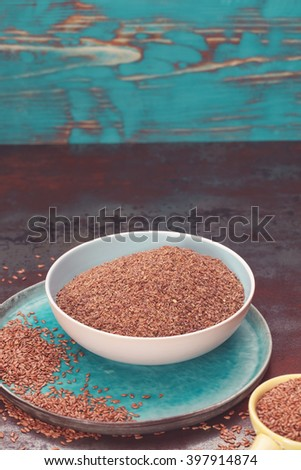 Flax seeds in bowl. Whole and ground flax seed  in ceramic dishes and  spoon.  Macro, selective focus, vintage toned image - stock photo