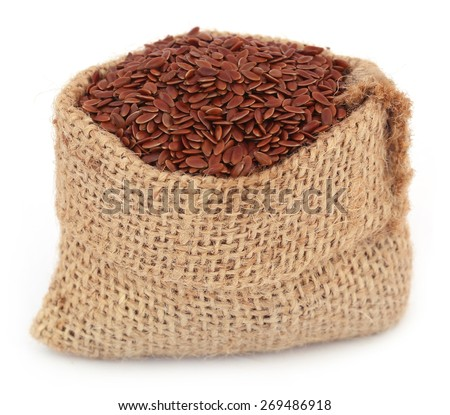 Flax seeds in jute bag over white background - stock photo
