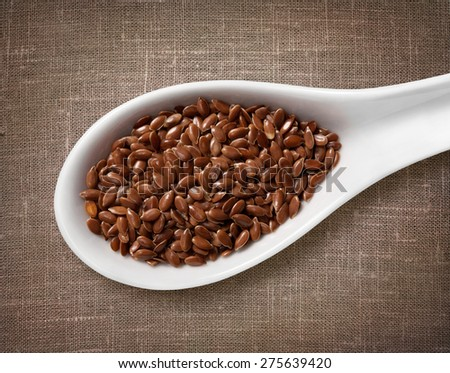 Flax seeds in white porcelain spoon / high-res photo of grain in white porcelain spoon on burlap sackcloth background - stock photo