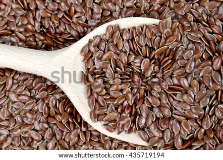 Flax seeds in wooden spoon on background - stock photo