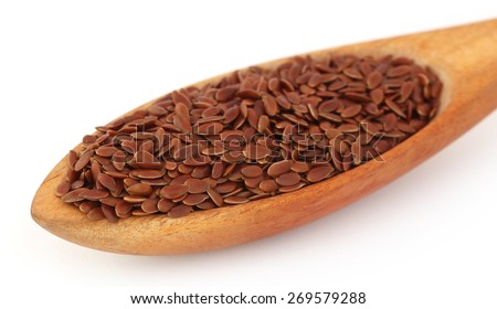 Flax seeds in wooden spoon over whtie background - stock photo