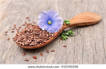 Flax seeds with flowers close up on wooden texture. - stock photo