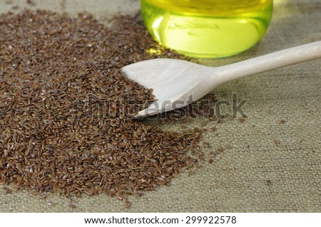 flax seeds with spoon and oil on canvas - stock photo