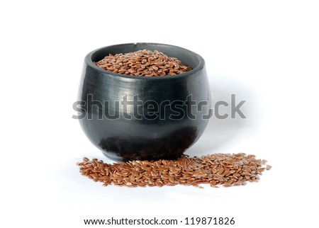 Flaxseed and a black ceramic cup isolated on a white background