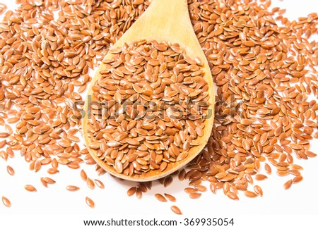 flaxseed on white background with a wooden spoon