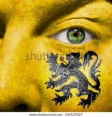 Flemish flag painted on a a man's face to support his region Flanders
