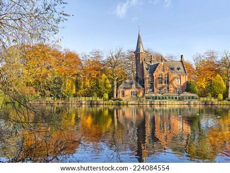 Flemish style building reflecting in Minnewater lake, Bruges, Belgium - stock photo