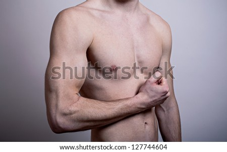 Flexed biceps. Strong young guy. - stock photo