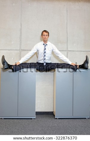 flexible business man in straddle, split position on cabinets - stock photo