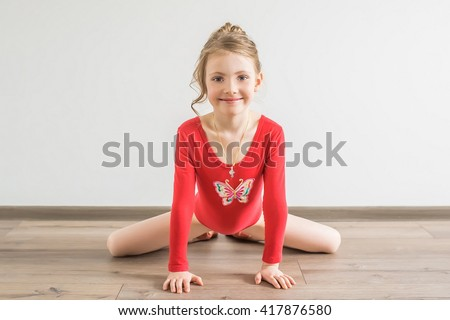 Flexible little girl in red leotard doing gymnastic - stock photo
