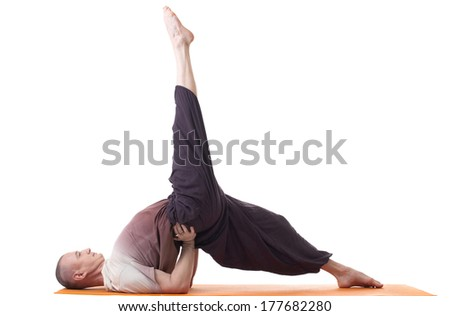Flexible man practicing yoga exercises in studio