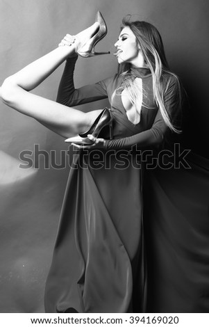 Flexible young fashionable woman with long beautiful hair in elegant dress holding raised leg in glamour shoes licking heel with tongue on studio background, vertical picture