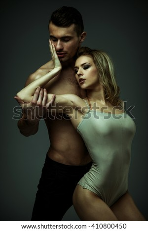 Flexible young modern acrobats couple posing in studio. Fashion portrait of attractive dancing couple. Man and woman. Passion. Love. perfect skin facial and make-up, blonde hair. The guy's pumped abs.
