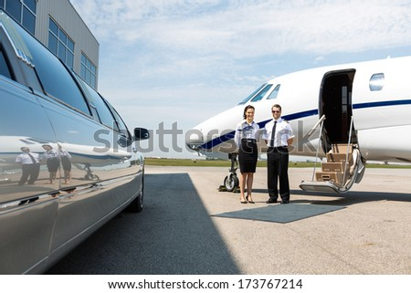 Flight attendant and pilot standing neat limousine and private jet at airport terminal - stock photo