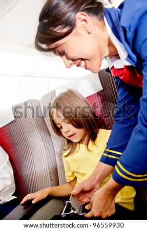 Flight attendant helping a kid to fasten his seatbelt - stock photo