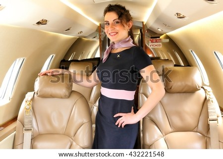 Flight attendant with the arm on the chair of the business jet - stock photo