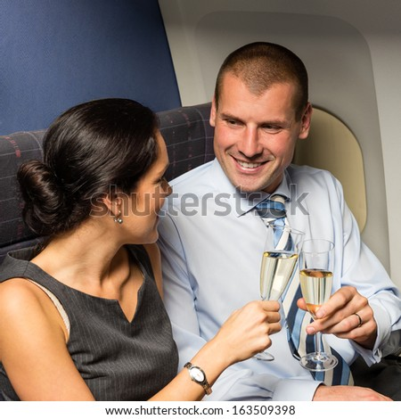 Flight cabin business partners toasting champagne airplane travel passengers - stock photo