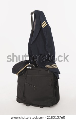 Flight crew uniform and hat hanging on trolley baggage on white background - stock photo