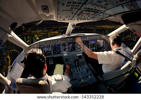 Flight Deck of modern passenger jet aircraft. Pilots at work. Night city view from the plane cockpit.