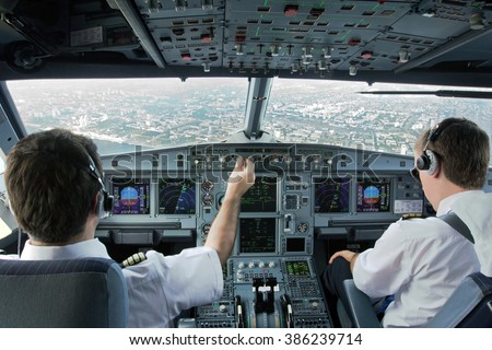 Flight Deck of modern plane.The pilots (cockpit crew) of aircraft prepares for landing at the airport. - stock photo