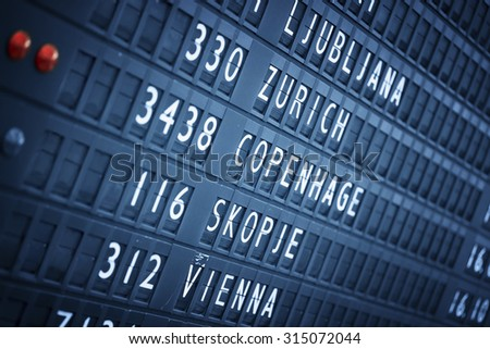 Flight information board in airport terminal. Travel background. - stock photo