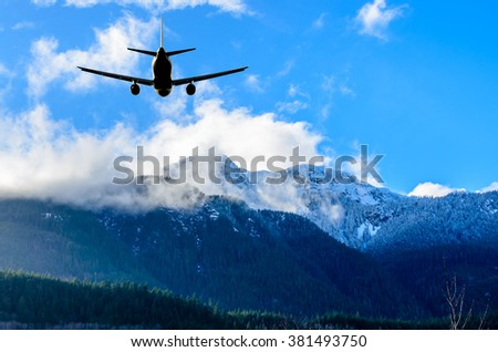 flight of the airplane (jet) over beautiful sky and snow mountains - stock photo