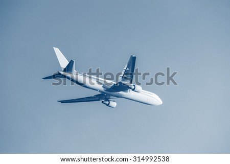 Flight of the passenger plane at sunset time. - stock photo