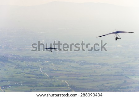 Flight over mountains. Hang-glider. Hang-glider flight over mountains. Hang-glider sport. Gliding sport. - stock photo