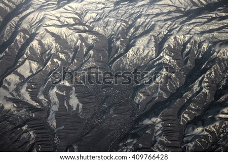 Flight over Pamir and Tien Shan 1. Air travel. Visible deep mountain valley and multitude of parallel ridges. Spring mountains and tree-like patterns of snow - stock photo