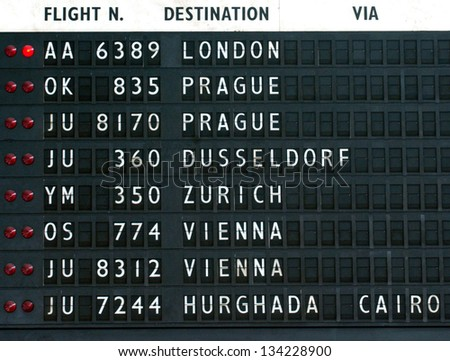 flight schedule board at airport terminal - stock photo