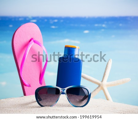 Flip-flop, lotion, starfish and sunglasses - summer accessories - stock photo